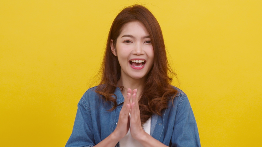 Portrait young Asian lady with positive expression, joyful and exciting, dressed in casual cloth and looking at camera over yellow background. Happy adorable glad woman rejoices success. Slow motion. | Shutterstock HD Video #1047226291