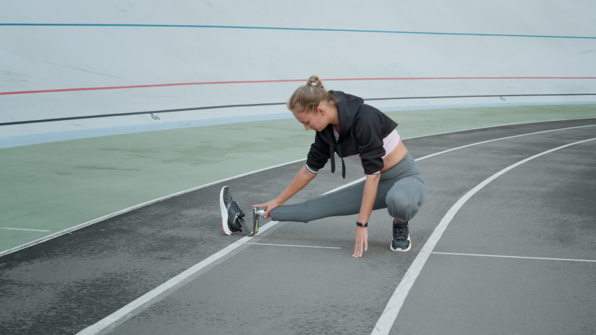 Disabled woman stretching legs on running track. Sporty lady preparing for workout outdoors in slow motion. Female runner with prosthetic leg exercising at sports stadium | Shutterstock HD Video #1047231631