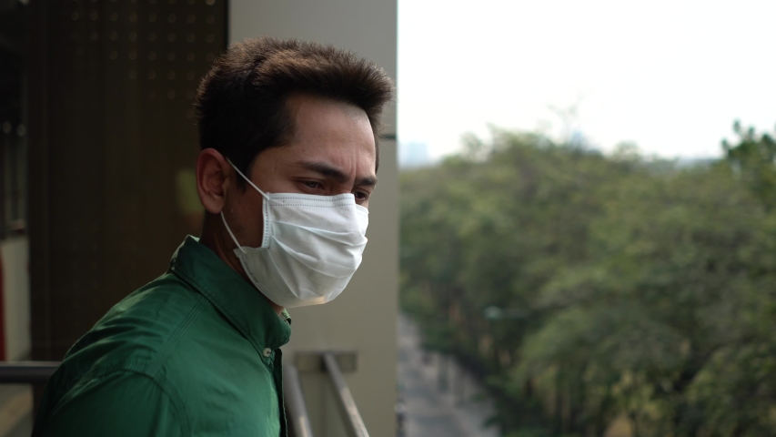 A man wearing mask protective for spreading of disease virus Covid-19 and air smog pollution with PM 2.5 with coughing on skywalk at Chatuchak district in  Bangkok city, Thailand. | Shutterstock HD Video #1047323371