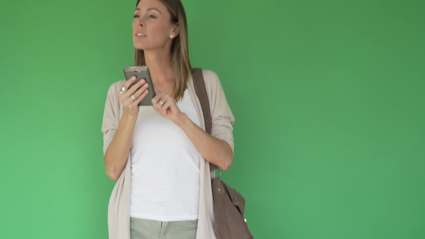 Woman walking with purse and smartphone, green screen | Shutterstock HD Video #1047332731