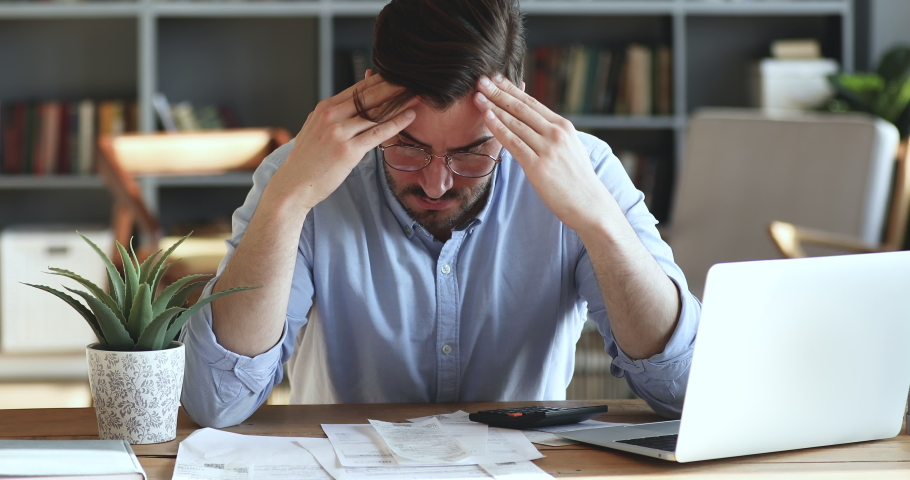 Depressed desperate man feeling worried about financial problem doing paperwork. Stressed businessman looking frustrated thinking of money debt, budget loss, bankruptcy sitting at home office desk.   Shutterstock HD Video #1047963091