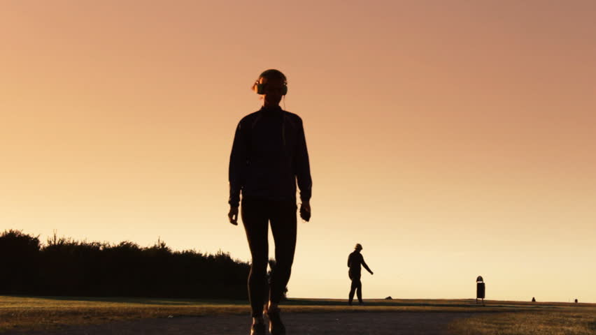 Sunset Young attractive woman  walking and listening music on headphones #10480811