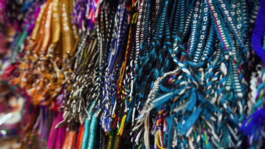 Colorful handcrafted goods hang outside a store in La Paz, Bolivia | Shutterstock HD Video #1048391581
