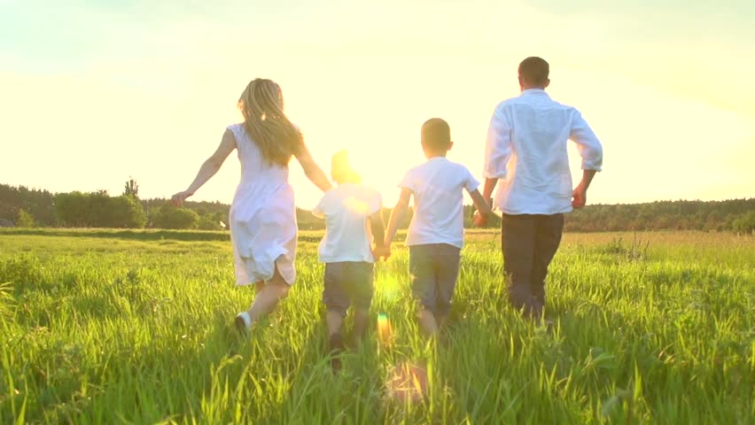 Happy Young Family with two children running on summer field. Healthy mother, father and little sons enjoying nature together, outdoors. Sunset. Slow motion 240 fps, high speed camera, Full HD 1080p