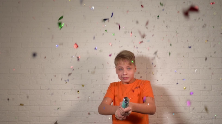 Young white kid using holiday festive popper full of sparkling shiny colorful confetti. | Shutterstock HD Video #1049515981