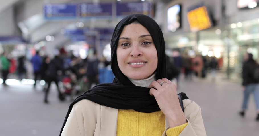 Smiling woman wearing hijab looking at camera at station | Shutterstock HD Video #1049571511