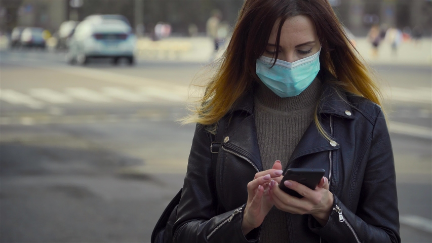 Woman in protective face mask typing messages on mobile phone in middle of city square while corona virus pandemic started. Dangerous COVID-19 infection | Shutterstock HD Video #1049575111