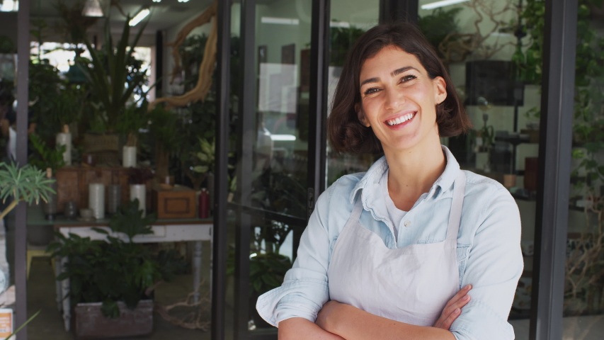 Female owner of florists shop standing in doorway of store looking into camera and smiling - shot in slow motion | Shutterstock HD Video #1049582251