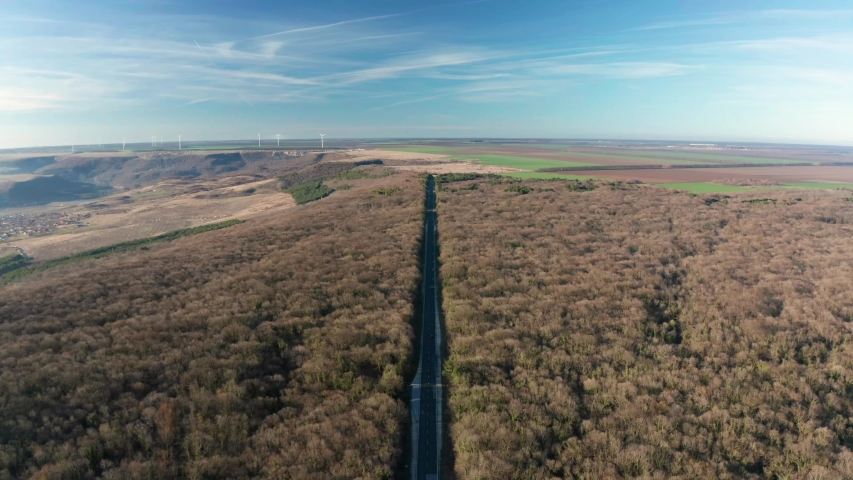 Drone flight over thick autumn forest with road and cars and wind farm in the distance  | Shutterstock HD Video #1049654551