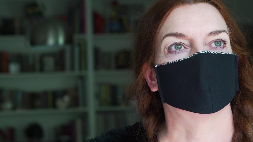 Portrait of an an experienced fashion designer wearing the face mask that she created at home  from recycled fabric as a protection against viruses, disease and germs | Shutterstock HD Video #1049712421