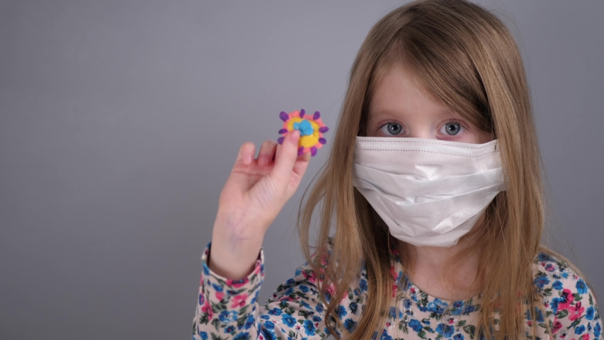 Portrait of a little blond girl in a protective mask holds and examines a model of coronavirus, a child performs research work at home schooling. | Shutterstock HD Video #1049712481