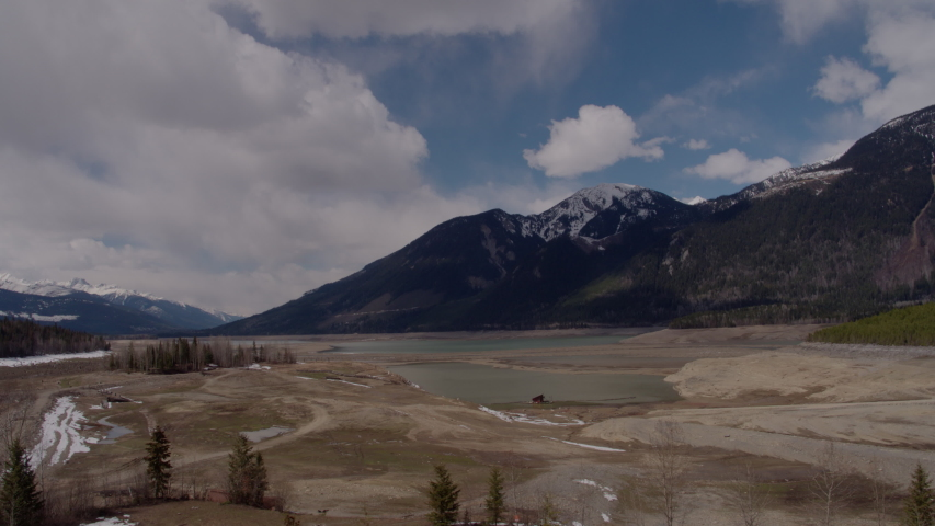 Aerial - Drone Dried Up Reservoir With Big Mountains in Background Kinbasket BC Canada | Shutterstock HD Video #1049716441