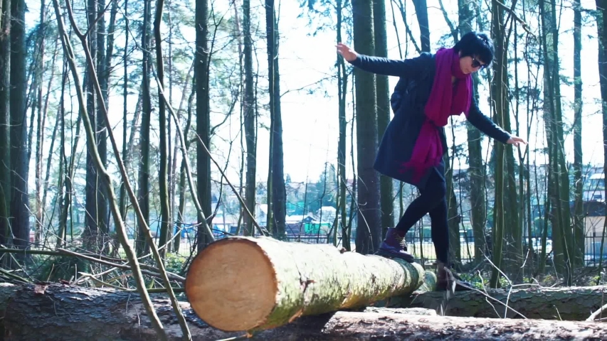 Mom with her son balance on a tree log in the forest. Active lifestyle in the fresh air. Adaptation of social distance. Social distance in the fresh air. | Shutterstock HD Video #1049763511
