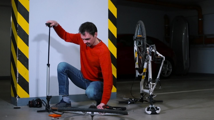 A man shakes a bicycle wheel in a garage at home. Preparing for a bike ride. Organization of social distance.  Quarantine COVID 19. | Shutterstock HD Video #1049781361