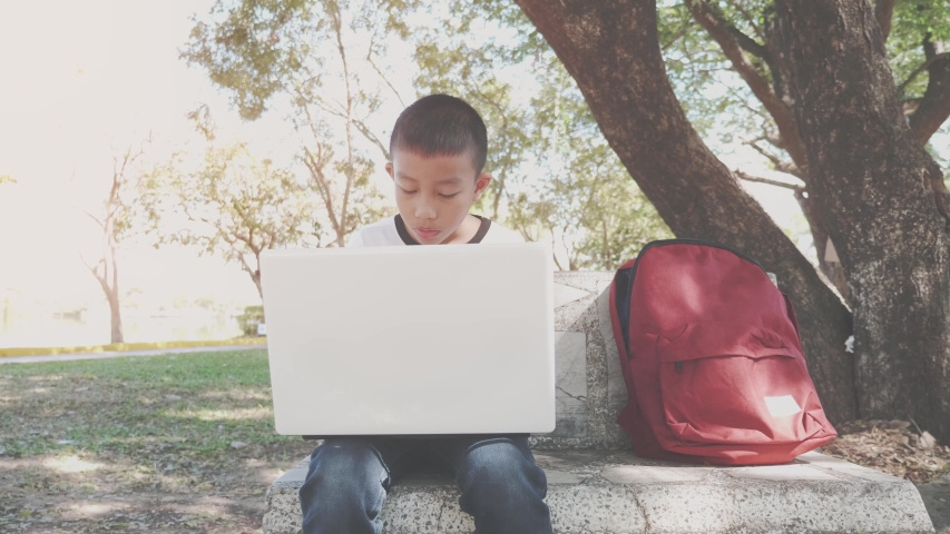 Back to School. asian boy using his laptop to learning online.  | Shutterstock HD Video #1049790751