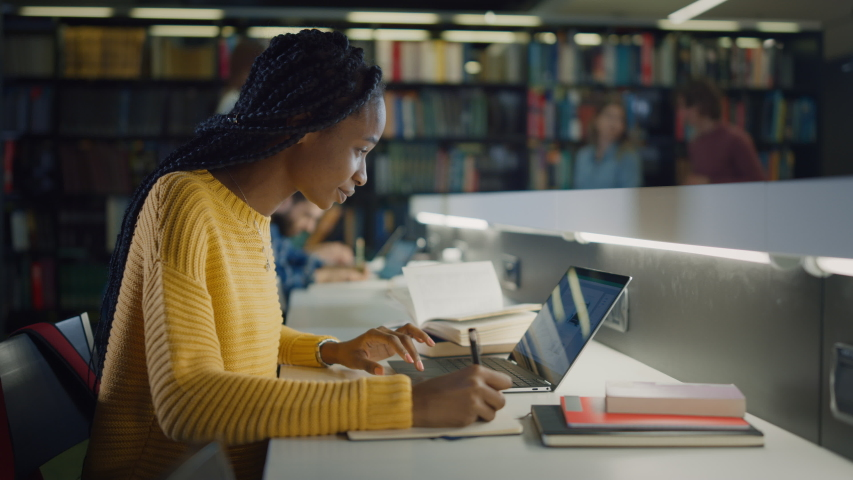 University Library: Gifted Beautiful Black Girl Sitting at the Desk, Uses Laptop, Writes Notes for the Paper, Essay, Study for Class Assignment. Diverse Group of Students Learning, Studying for Exams. | Shutterstock HD Video #1049866981