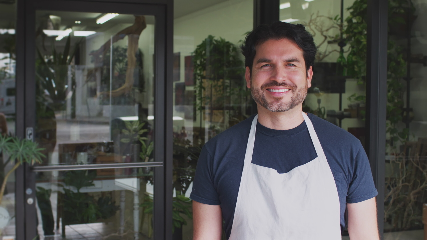 Male owner of florists shop standing in doorway of store looking into camera and smiling - shot in slow motion | Shutterstock HD Video #1049872981