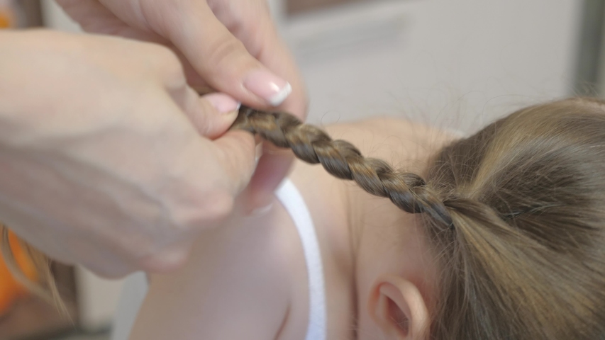 Mom Braids Braid Of Her Little Daughter. mother combs the child's hair with a comb. concept of beautiful hairstyle for daughter. a happy family. | Shutterstock HD Video #1049993641