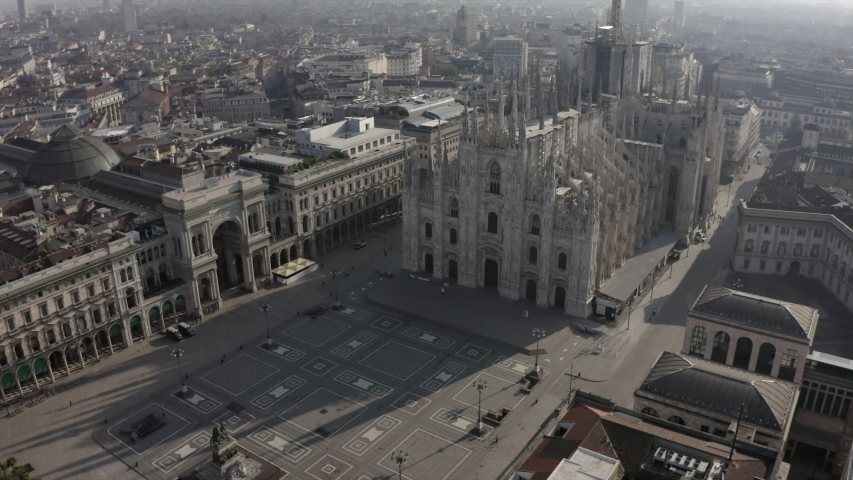 Daily life in Milan, Italy during COVID-19 pandemic. Milano, Italian city and coronavirus outbreak. Aerial view of Piazza Duomo. Historic monument and religious bulding seen from drone flying in sky | Shutterstock HD Video #1050084151