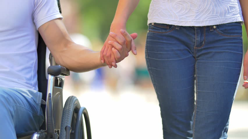 The woman walk and take the disabled man's hand (man is in the wheelchair). Social video. Shot with Red Cinema Camera