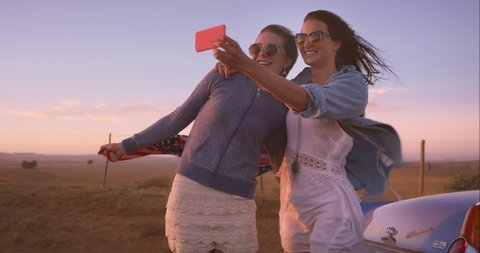beautiful Girl friends taking selfies on road trip at sunset with vintage car RED DRAGON