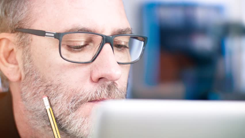 Man with glasses working on laptop computer | Shutterstock HD Video #10523381