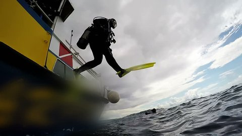 Scuba Diver Jumping Off Dive Boat. High speed camera shot. In slow motion a scuba diver jumps into water.