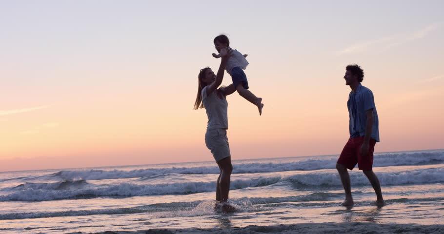 Mother swinging little girl around Happy family on the beach holding hands sat sunset on vacation slow motion RED DRAGON