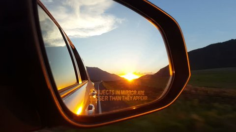 SANPETE COUNTY. UTAH - JUNE 2015: A beautiful orange and yellow sunset glows in the rear view mirror of an eastbound auto as it drives through a low mountain pass