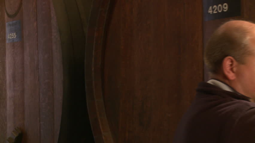 Wine maker in ancient cellar tasting his creation. Tracking shot