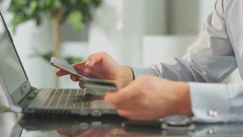 Man inserting credit card number on mobile phone, online banking. Office worker paying bills in internet, modern technology connection. Guy booking hotel by smartphone application, shopping, finance