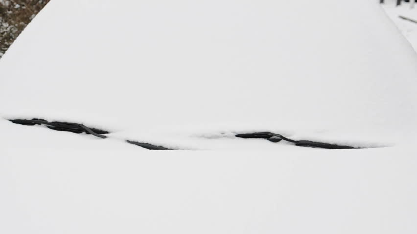 Pair of windscreen wipers clearing the windscreen of a car that is covered with snow
