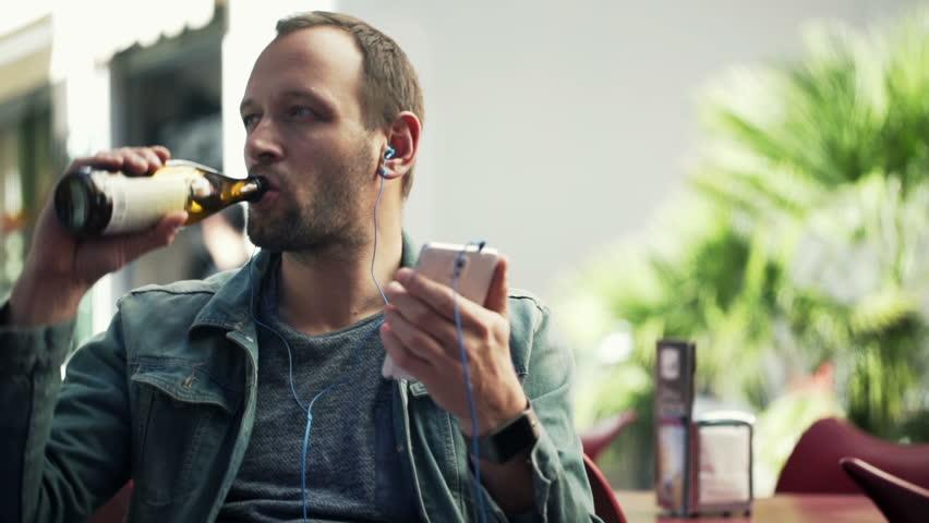Young man in earphones listen to the music, drink beer in cafe  | Shutterstock HD Video #10571681