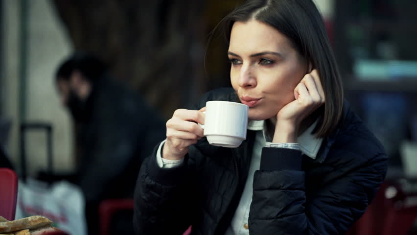 Sad, pensive woman drinking coffe cafe in the city  | Shutterstock HD Video #10571684
