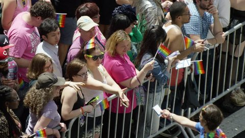 NEW YORK - JUNE 28, 2015: woman handing girl safe-sex condom pack behind police barrier, lesbian sharing at gay pride parade, slow motion 4K, NYC. US is the 21st country to legalize same-sex marriage.