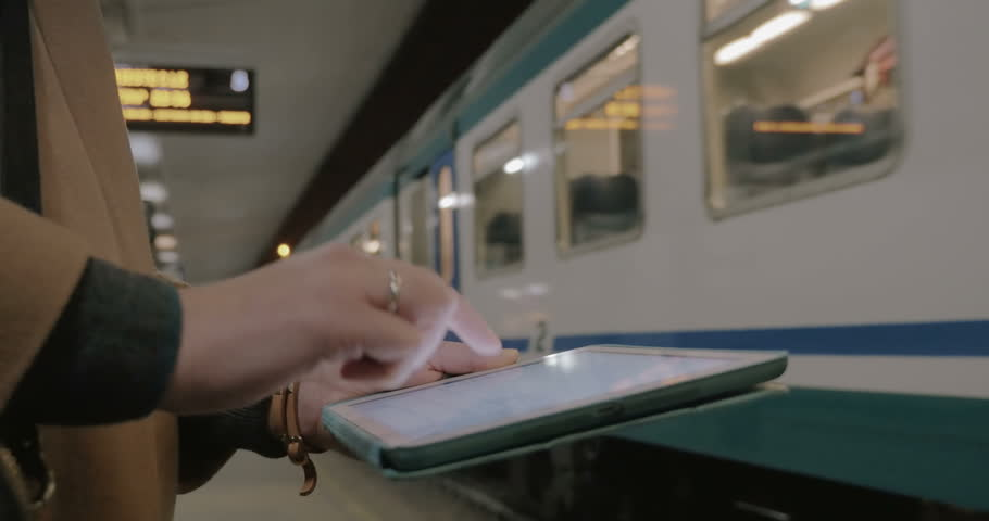Close-up shot of a woman using pad in the underground. She typing and sending message standing on the platform by the leaving train | Shutterstock HD Video #10598591