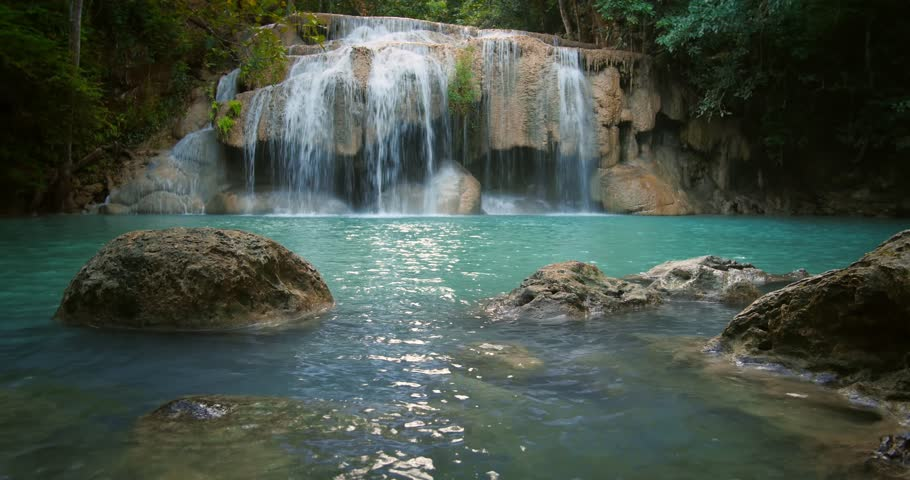 Erawan waterfall in Thailand. Peaceful natural background with beautiful waterfall in jungle rainforest with wet stones in water and natural pond pool