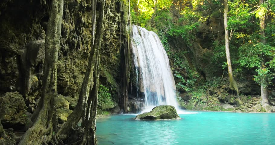 Tranquil and serene scene of waterfall falling in wild pond in jungle rainforest of Asia