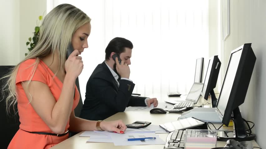 Woman and man phone and work on desktop computer in the office - support - telephone | Shutterstock HD Video #10607231