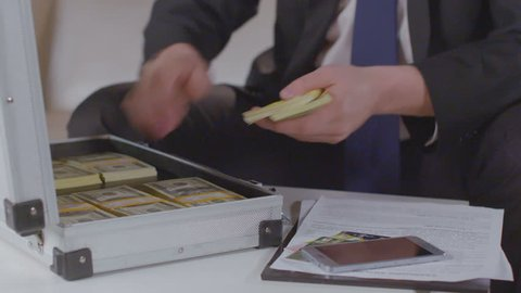 Closeup male hands open briefcase with money, take dollar packs