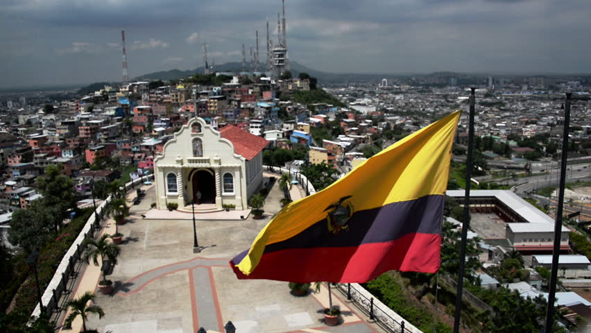 Ecuadorian flag waving in front of a church with Guayaquil in the background in Ecuador