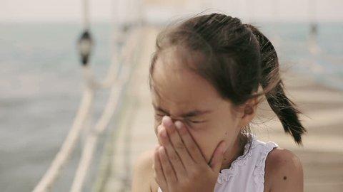 Child sneezes on pier in ocean