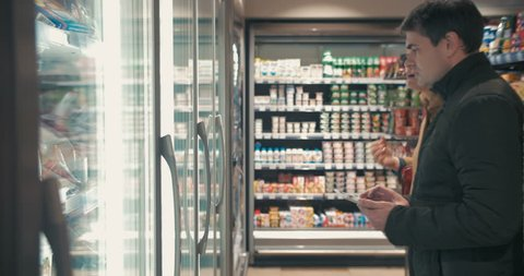 Young people choosing food in fridge section of the supermarket. Woman taking two packages of frozen strawberries, while man checking shop list on the pad