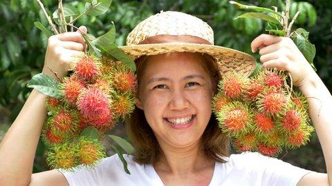 Young Asian farmer holding rambutan on her farm in Thailand