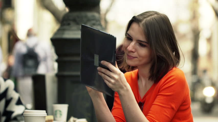 Young woman using tablet computer while sitting in cafe in city  | Shutterstock HD Video #10646924