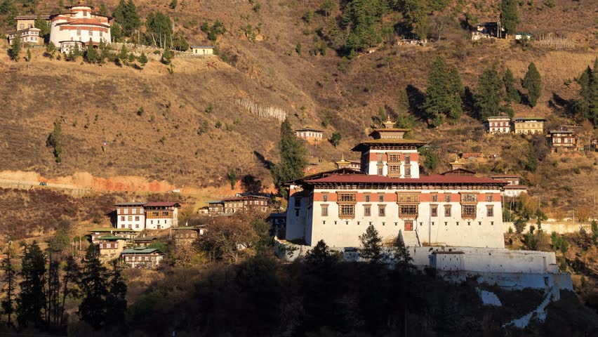 Timelapse of The Paro Rinpung Dzong and The Ta Dzong (Bhutan National Museum) on the mountain in evening of late autumn, Paro, Bhutan.