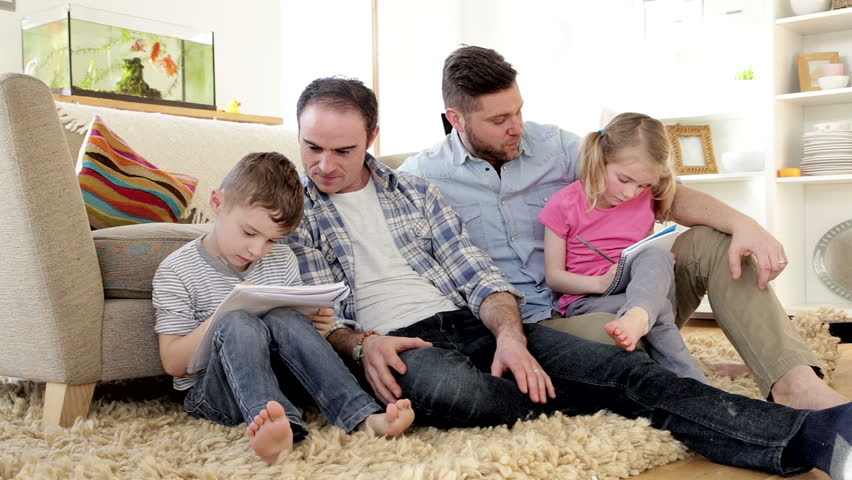 Male couple helping their son and daughter do their homework. They are sitting against a sofa in their home.   Shutterstock HD Video #10674710
