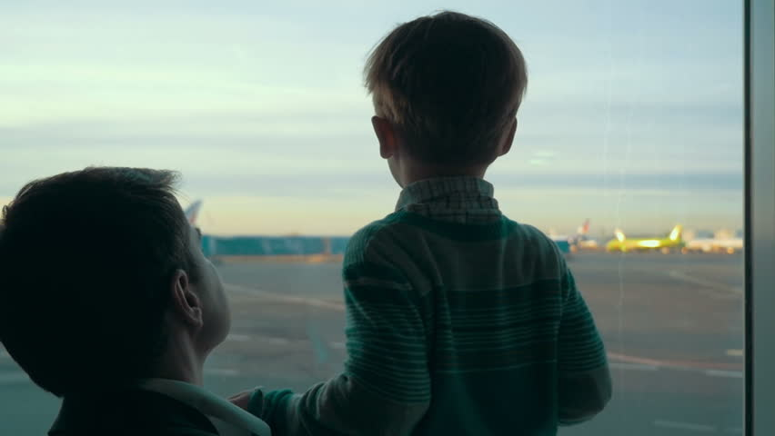 Slow motion of father and son looking out the window with view on airport area. Truck passing by, planes can be seen in the distance