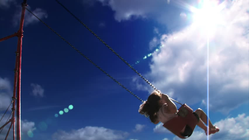 A young girl swings on a swing set in a playground  Low angle with the sky shown prominently. #1068931