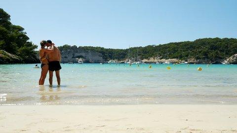 Intimate Middle aged couple hugging on beach Cala Galdana Menorca